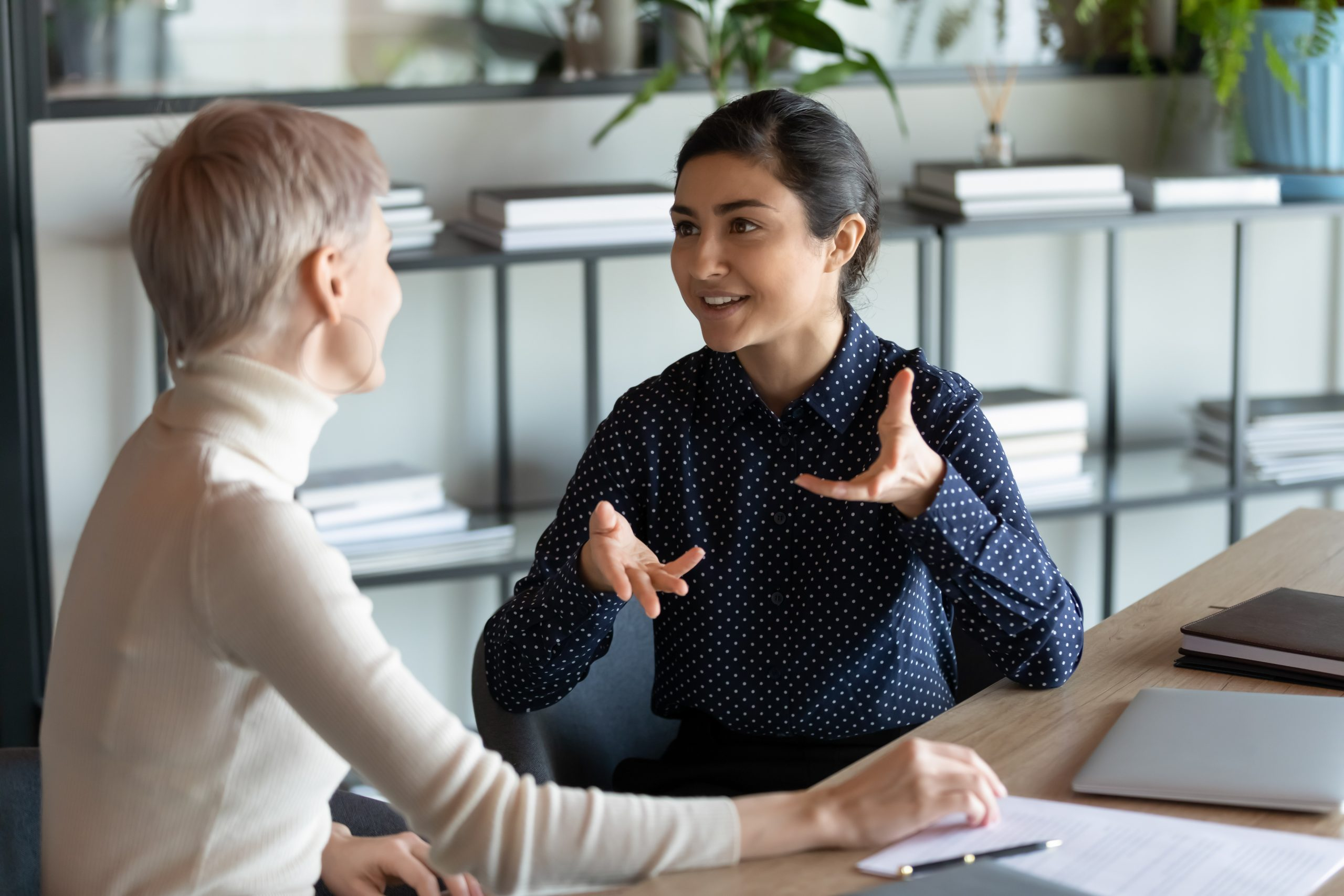 Indian female employee talking with Caucasian mate seated at workplace desk expresses her opinion on current issue, proposes solution to problem, share thoughts while working on common project concept